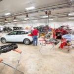 Man repairing car inside of garage